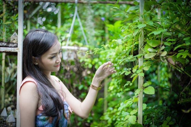 La muchacha bonita asiática tiene la relajación con feliz y sonrisa en poco café del jardín del árbol, provincia de Nakhon Pathom fotografía de archivo
