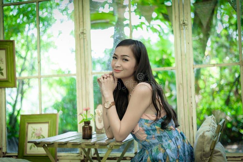 La muchacha bonita asiática tiene la relajación con feliz y sonrisa en poco café del jardín del árbol, provincia de Nakhon Pathom fotos de archivo