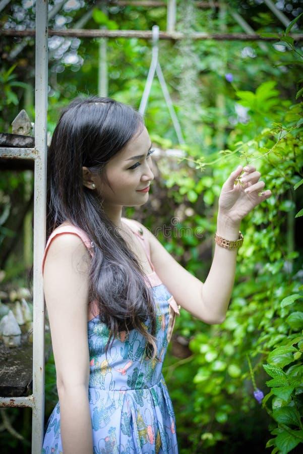 La muchacha bonita asiática tiene la relajación con feliz y sonrisa en poco café del jardín del árbol, provincia de Nakhon Pathom imagen de archivo libre de regalías