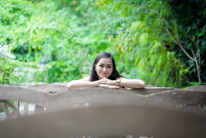 La muchacha bonita asiática tiene sentarse con feliz y relajación en el pequeño café del jardín del árbol, provincia de Nakhon Pa foto de archivo