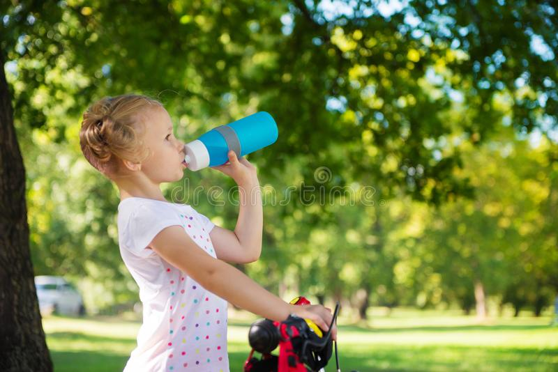 La muchacha bonita con la bicicleta bebe el agua en parque del verano foto de archivo