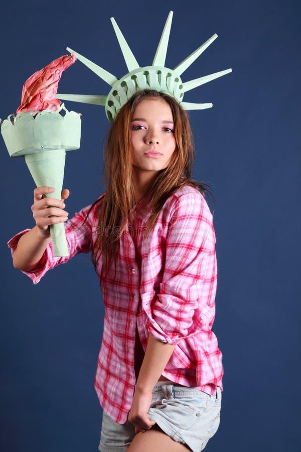 La muchacha bonita con la corona y la antorcha representa la estatua de la libertad foto de archivo libre de regalías
