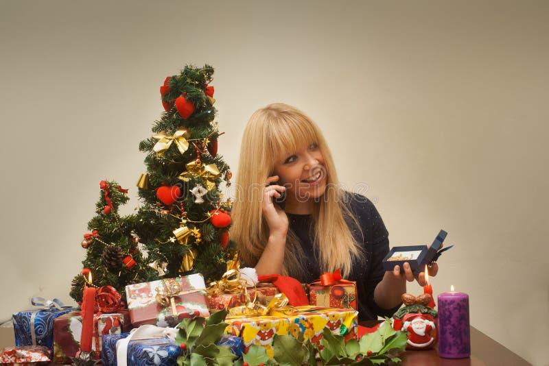 La muchacha bonita consigue jewellry para el regalo de la Navidad y sonríe imagen de archivo