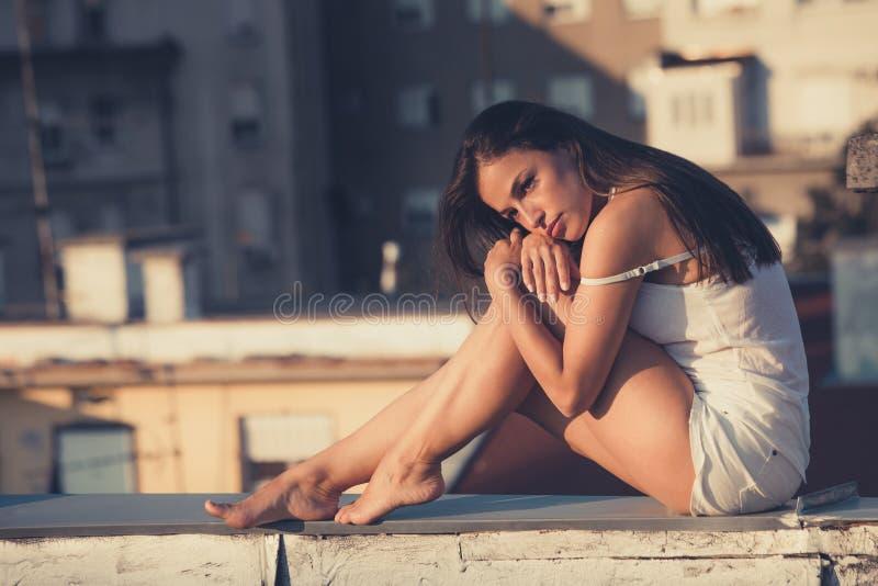 La muchacha bonita de la ciudad goza en puesta del sol en el tiro lleno summ del cuerpo del tejado fotos de archivo libres de regalías
