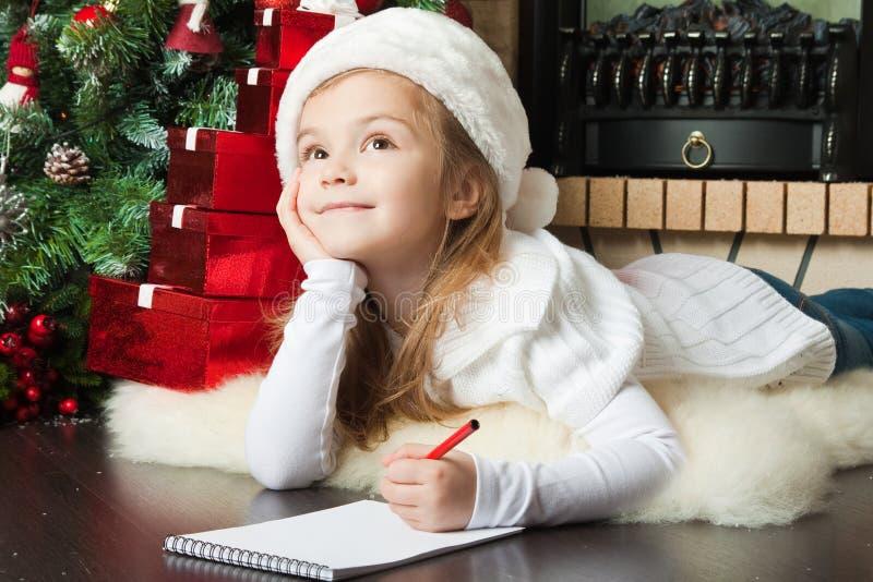 La muchacha bonita en el sombrero de Santa escribe la letra a Santa fotos de archivo