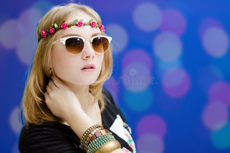 La muchacha bonita en gafas de sol y la flor enrruellan encendido fotos de archivo libres de regalías