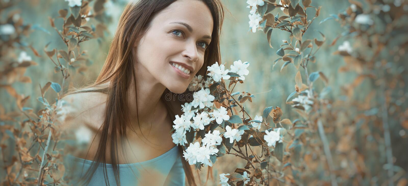 La muchacha bonita feliz se está sentando en hierba verde fotografía de archivo libre de regalías