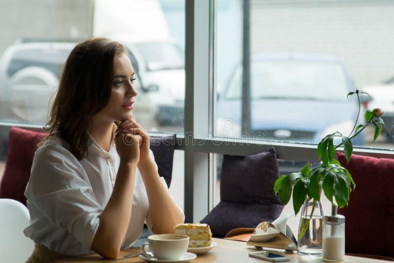 La muchacha bonita goza de un café fragante y de una torta dulce que se sientan en café Mujer de negocios que descansa durante ro foto de archivo libre de regalías