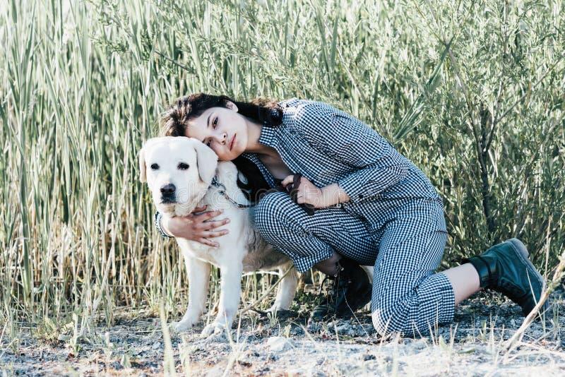 La muchacha bonita joven abraza su perro contra un fondo de la hierba verde imagenes de archivo