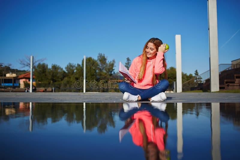 La muchacha bonita pasa tiempo al aire libre en el parque que lee un libro y que come una manzana verde imágenes de archivo libres de regalías