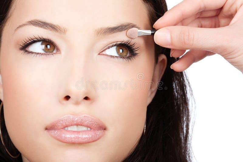 La muchacha bonita recibe el sombreador de ojos de artista de maquillaje imágenes de archivo libres de regalías