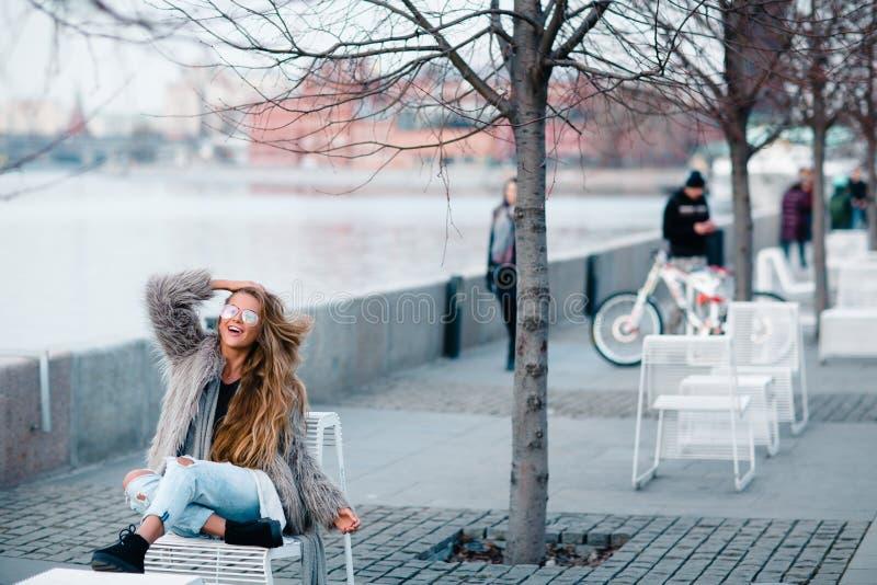 La muchacha bonita rubia feliz en capa y los vidrios se cierran encima del retrato imágenes de archivo libres de regalías