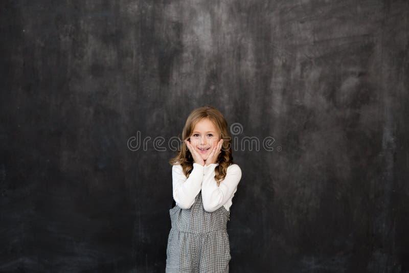 La muchacha bonita se coloca en el fondo negro de una pizarra y de una sonrisa imagen de archivo libre de regalías