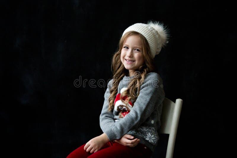 La muchacha bonita se coloca en el fondo negro de una pizarra y de una sonrisa fotografía de archivo libre de regalías