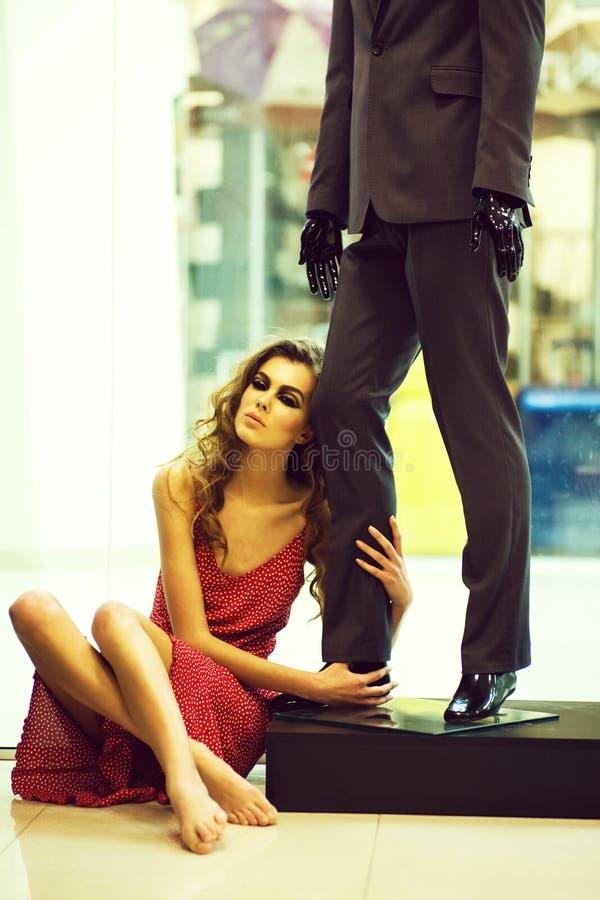 La muchacha bonita se sienta en piso en el maniqu? masculino en tienda imagen de archivo