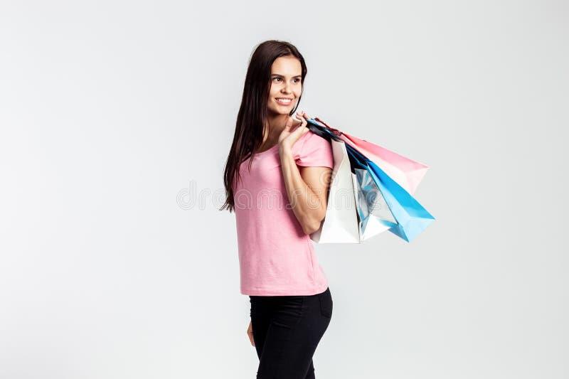 La muchacha bonita sonriente vestida en camiseta rosada y vaqueros está sosteniendo bolsos de compras en el fondo blanco en el es fotografía de archivo libre de regalías