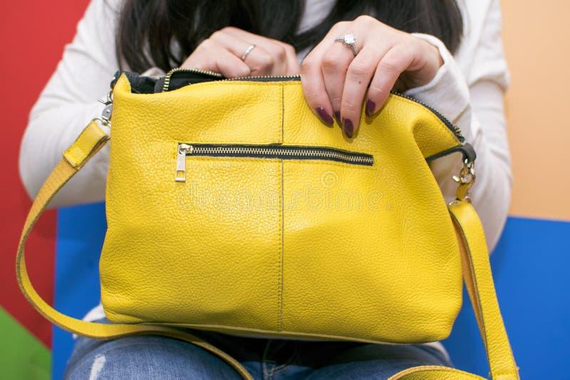 La muchacha busca para algo en su bolso Bolso del ` s de las mujeres fotos de archivo