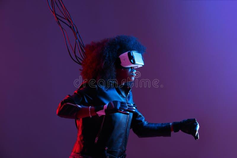 La muchacha cabelluda oscura rizada de la MOD vestida en chaqueta de cuero y guantes negros utiliza los vidrios de la realidad vi imagen de archivo