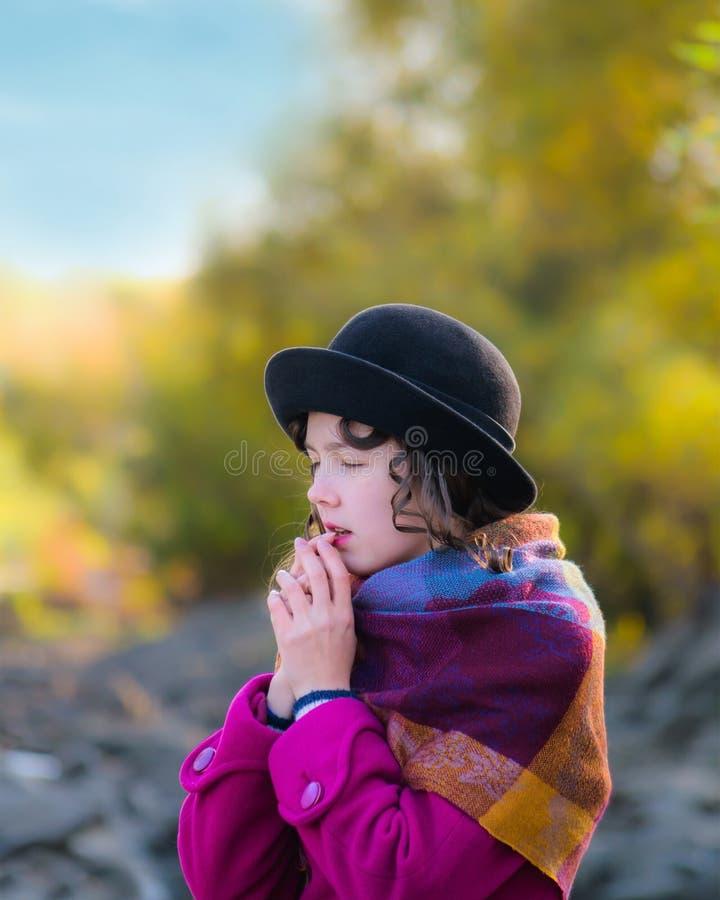 La muchacha calienta las manos que respiran para calentar imagen de archivo