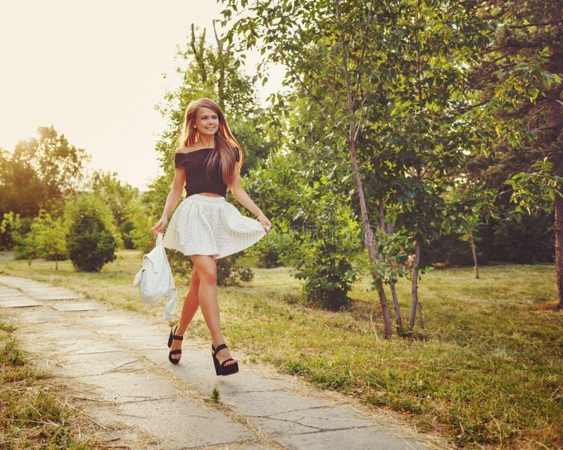 La muchacha camina con el bolso en parque foto de archivo
