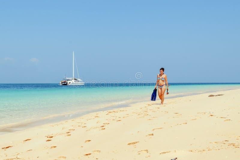 La muchacha camina en la playa con el engranaje que bucea con el catamarán adentro imagen de archivo libre de regalías