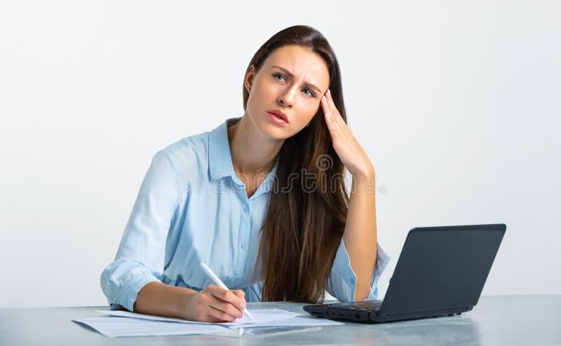 La muchacha cansada en la oficina decide foto de archivo