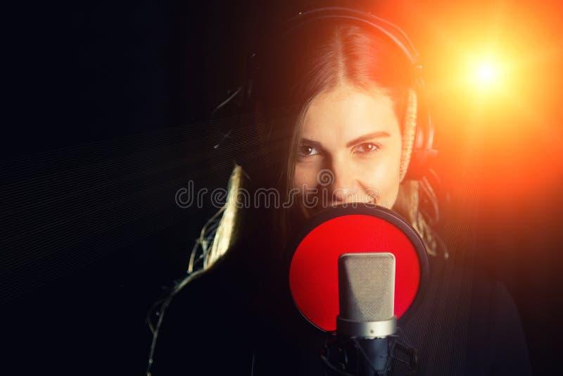 La muchacha cantante canta al micrófono profesional en el estudio de registro El proceso de crea una nueva canción de hit del can imagen de archivo