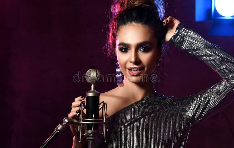 La muchacha cantante hermosa cantante afro rizado del pelo canta con la canción del Karaoke del micrófono en etapa en luz de neón imagen de archivo libre de regalías