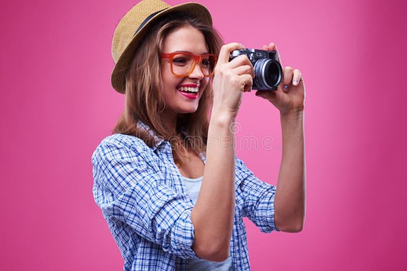La muchacha casual mira la lente de la cámara mientras que toma la foto foto de archivo