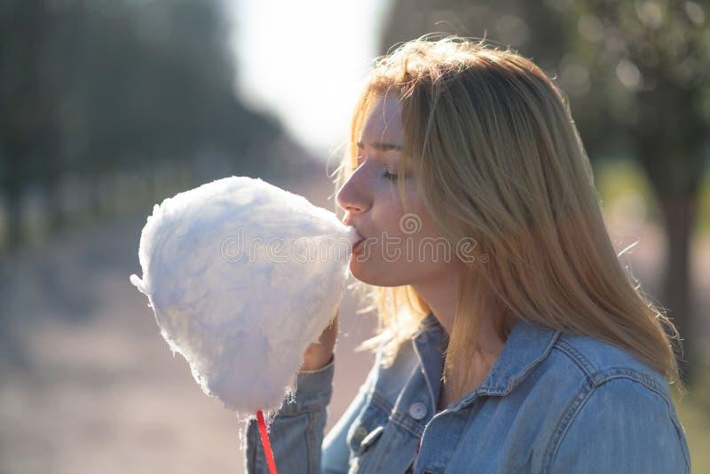 La muchacha caucásica encantadora camina en el parque de la primavera en una chaqueta del dril de algodón y come el caramelo de a imagen de archivo libre de regalías
