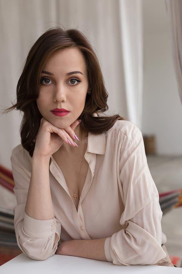 La muchacha caucásica hermosa con los labios rojos en blusa beige elegante mira cuidadosamente en la cámara, inclinándose en la t fotos de archivo libres de regalías