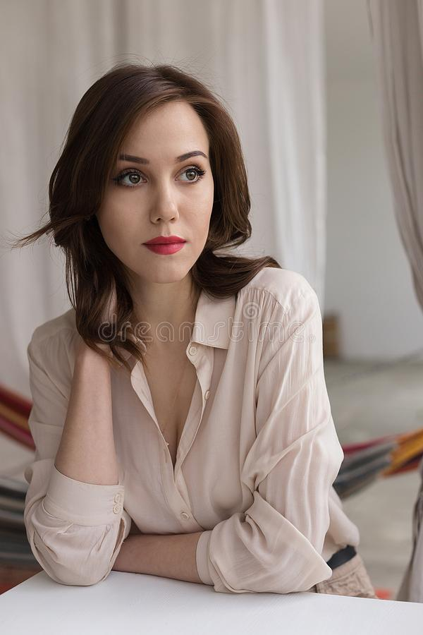 La muchacha caucásica hermosa con los labios rojos en blusa beige elegante mira cuidadosamente a un lado, inclinándose en la tabl fotos de archivo libres de regalías