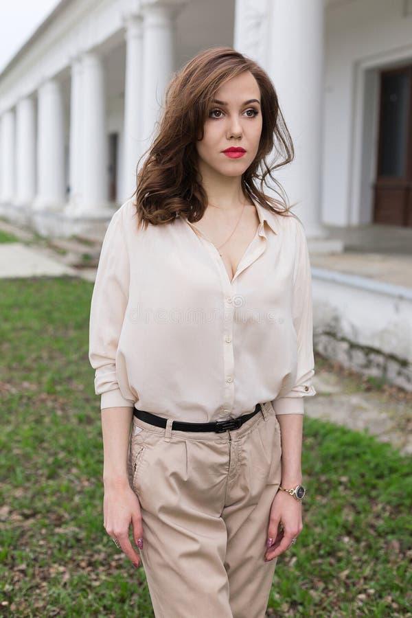 La muchacha caucásica hermosa con los labios rojos, pelo rizado en blusa beige elegante mira cuidadosamente a un lado Concepto de fotos de archivo libres de regalías