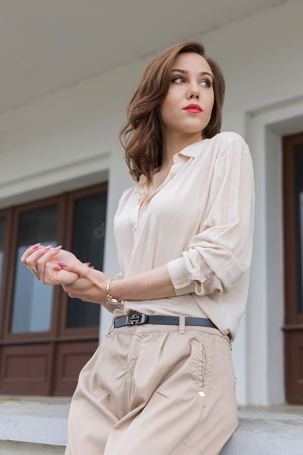 La muchacha caucásica hermosa con los labios rojos, pelo rizado en blusa beige elegante mira cuidadosamente a un lado Concepto de fotos de archivo