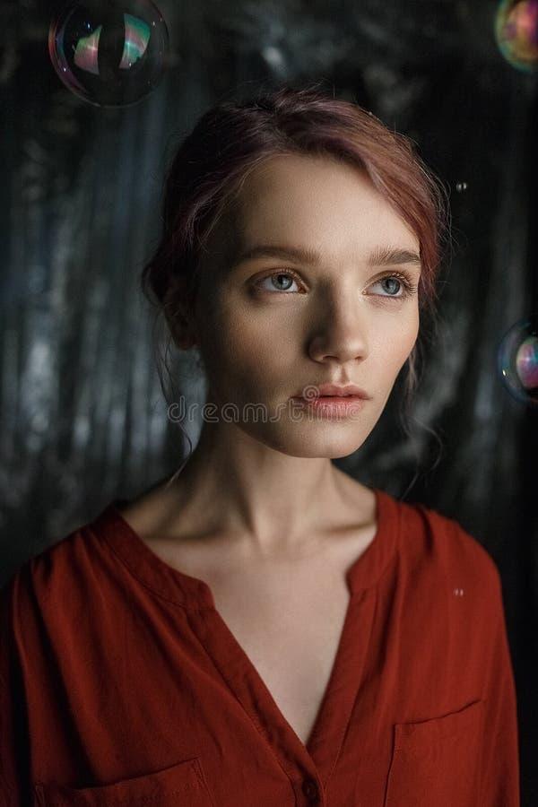 La muchacha caucásica joven bonita en camisa roja mira para arriba Las burbujas de jabón vuelan alrededor de su cabeza que riela  imágenes de archivo libres de regalías