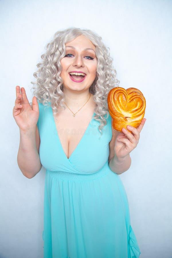La muchacha caucásica linda en un vestido azul se coloca con un bollo bajo la forma de corazón y sonrisas en un fondo sólido blan imagenes de archivo