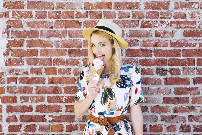 La muchacha caucásica rubia lame el helado contra un cono Fedora Hat de la pared de ladrillo fotos de archivo