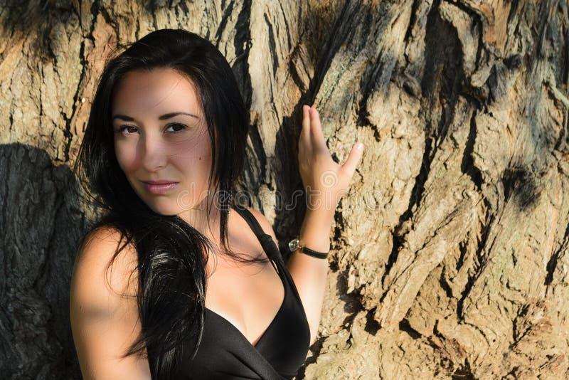 La muchacha cerca de un tronco de árbol foto de archivo libre de regalías