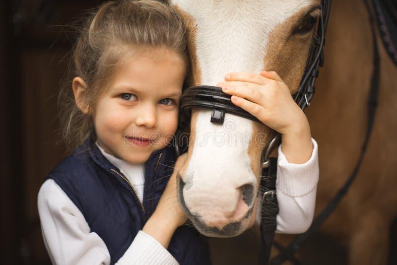 La muchacha cercana hermosa del retrato sienta el caballo del beiside en el puente Bosque en fondo Rebecca 36 imágenes de archivo libres de regalías
