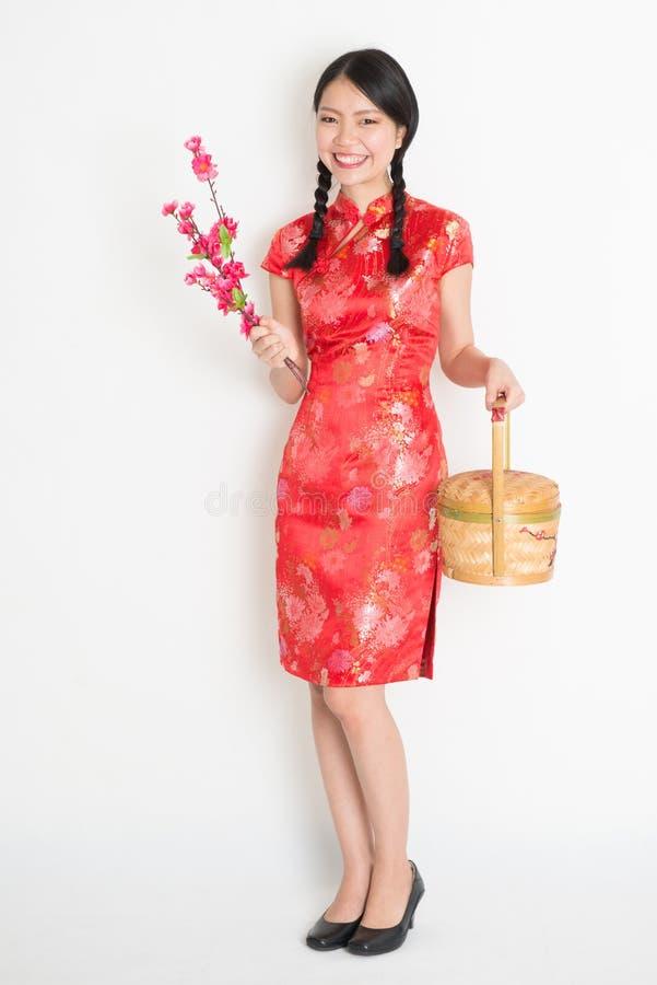 La muchacha china asiática que sostiene la cesta del regalo y el ciruelo florecen fotos de archivo