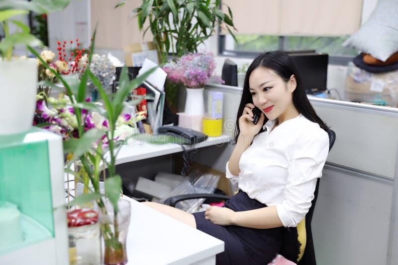La muchacha china de la mujer de la señora de la oficina de Asia en silla hace que un escritorio del uso de la llamada llama por  foto de archivo libre de regalías