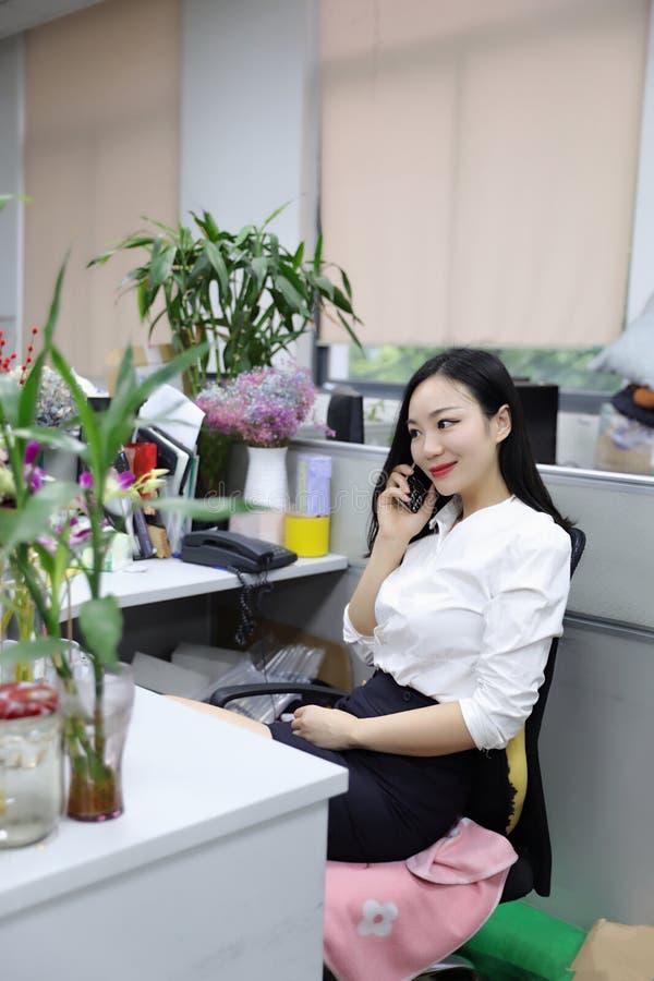 La muchacha china de la mujer de la señora de la oficina de Asia en silla hace que un escritorio del uso de la llamada llama por  fotos de archivo