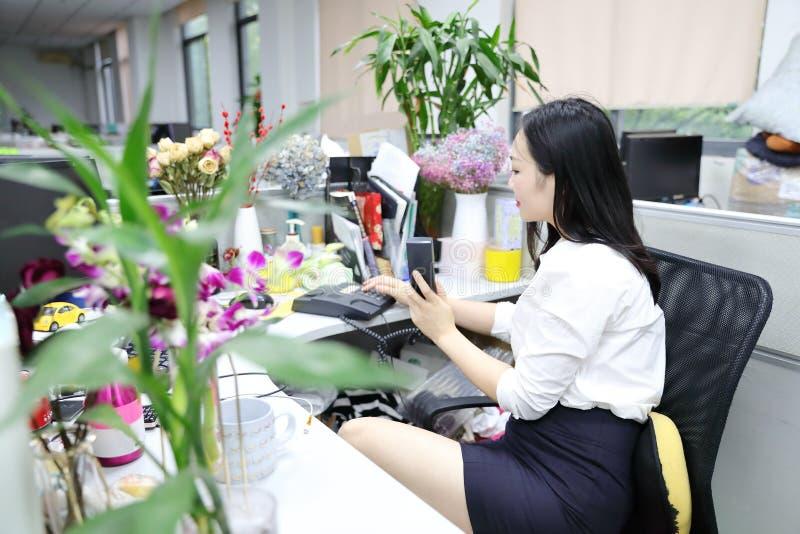 La muchacha china de la mujer de la señora de la oficina de Asia en silla hace que un escritorio del uso de la llamada llama por  imágenes de archivo libres de regalías
