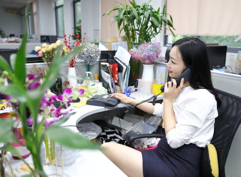 La muchacha china de la mujer de la señora de la oficina de Asia en silla hace que un escritorio del uso de la llamada llama por  imagen de archivo