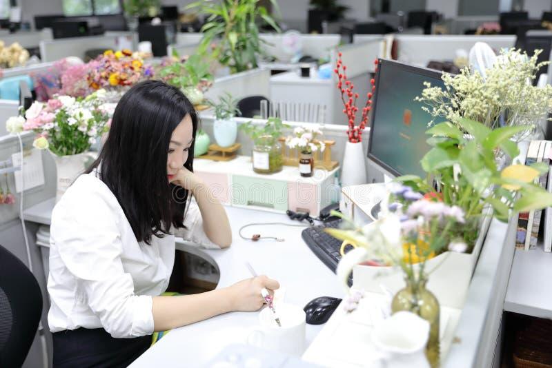 La muchacha china de la mujer de la señora de la oficina de Asia se sienta en silla toma notas en el lugar de trabajo del traje d foto de archivo