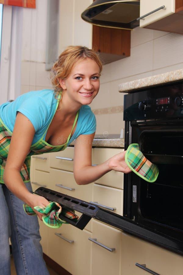 La muchacha cocina el alimento en un horno imágenes de archivo libres de regalías