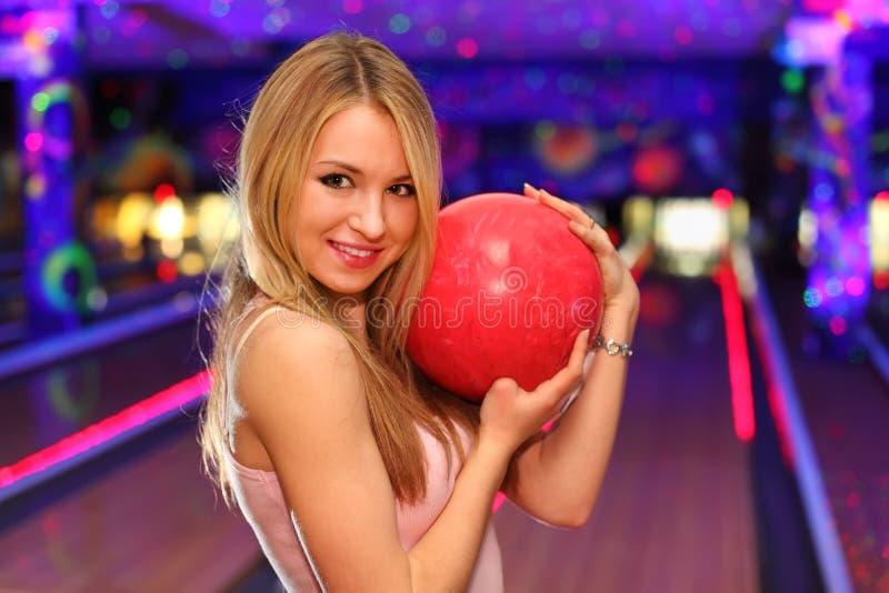 La muchacha coloca y abraza la bola en club del bowling foto de archivo libre de regalías