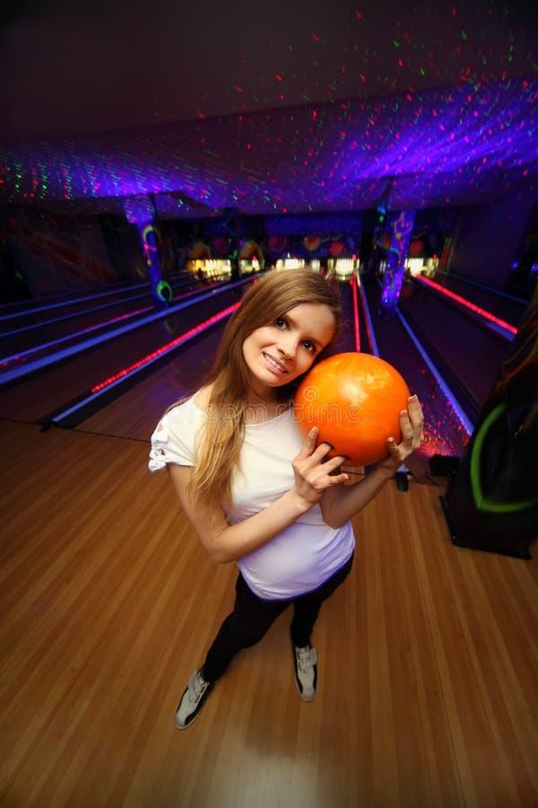 La muchacha coloca y abraza la bola en club del bowling fotos de archivo