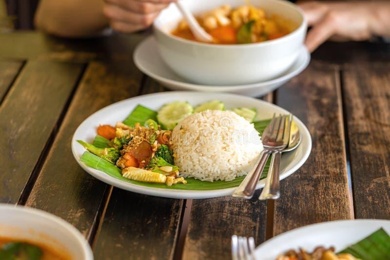 La muchacha come la comida tailandesa - sopa de Tom Yam y arroz tailandés con la guarnición imagen de archivo