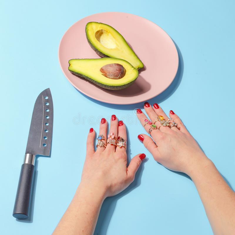 La muchacha come con un cuchillo y bifurca un pedazo de aguacate en una placa rosada Concepto de Minimalistic Visión superior foto de archivo libre de regalías